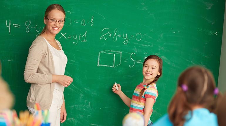 девочка и учительница возле доски, дети в школе на уроке,девочка отвечает возле доски
