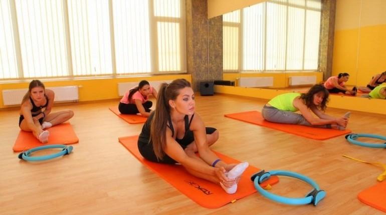 девушки в спортзале, упражнения на растяжку, йога, групповые занятия