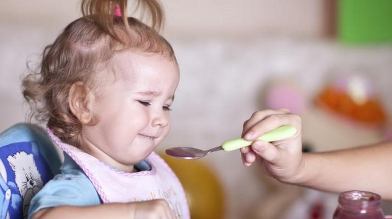 кормление ребенка с ложки, маленький ребенок кушает с ложки