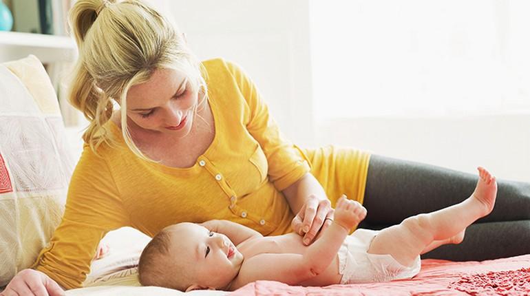 мама с новорожденным ребенком, младенец в памперсе и мама