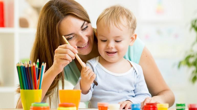 девушка играет с ребенком, малыш и няня улыбаются