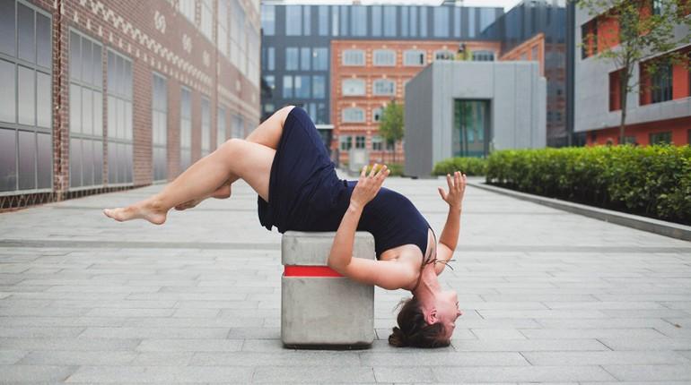девушка исполняет сложный акробатический трюк, танцы на голове