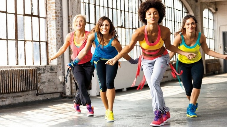 девушки танцуют зумбу,занятие в спортзале