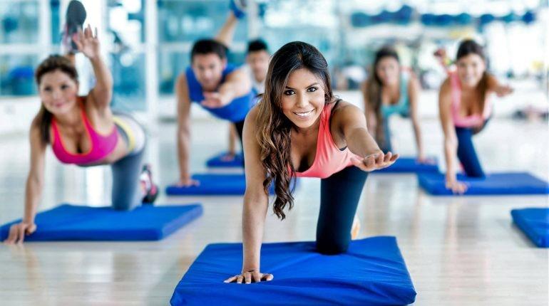 групповые занятия в спортзале, девушкана тренировке на коврике