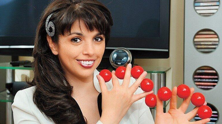 девушка показывает фокусы, симпатичная брюнетка и красные шары