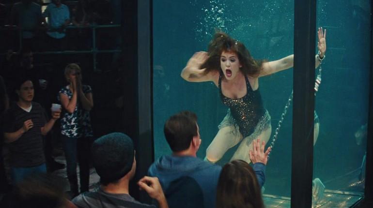 девушка плавает в аквариуме, зрители смотрят на девушку в аквариуме