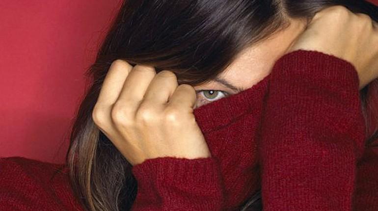 девушка закрыла лицо свитром, глаз девушки выглядывает из-под свитера