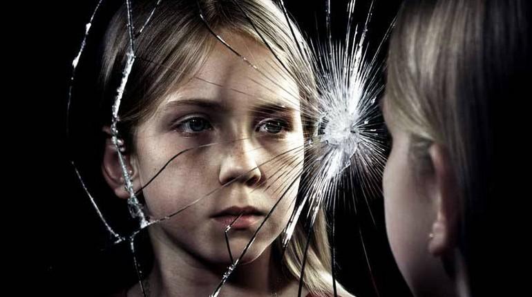 девочка смотрит через разбитое стекло, треснутое стекло и девочка