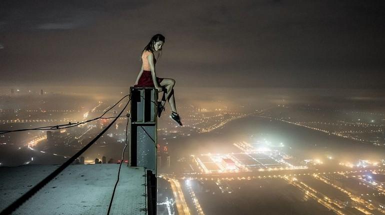 девушка сидит на крыше высокого здания, попытка суицида