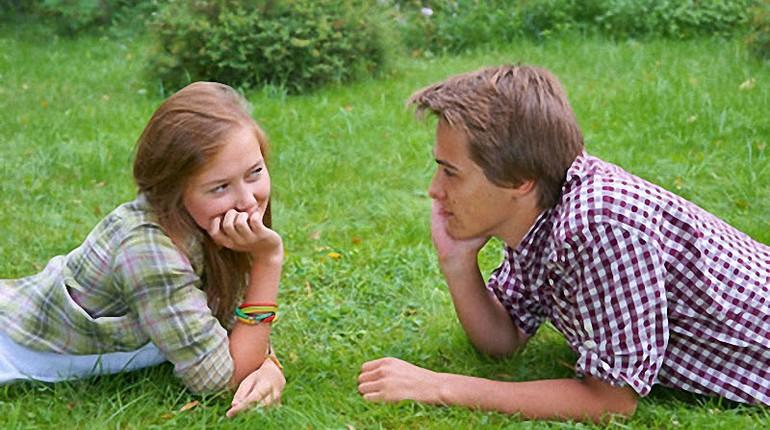 парень и девушка лежат на траве, парочка на траве летом, смотрят друг на друга