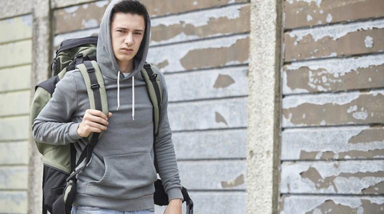парень с рюкзаком и в капюшоне идет по улице