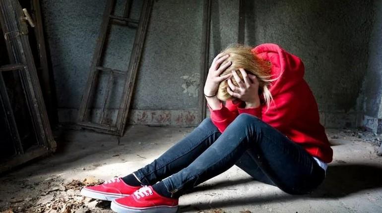 девушка в джинсах сидит на полу и держится за голову