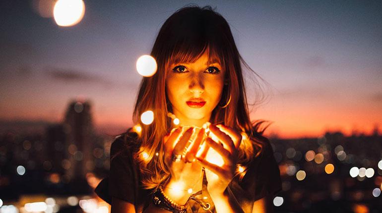 девушка держит огонь, свет в ладошках девушки