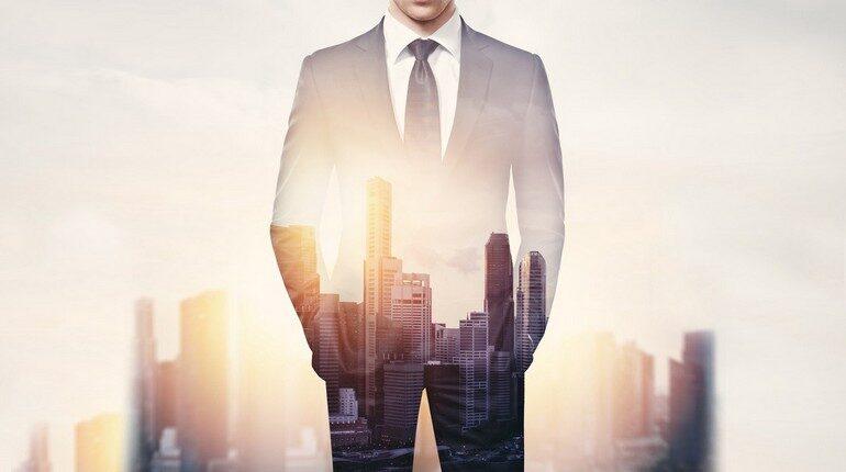 человек стоит на фоне небоскребов, солнечный свет проходит сквозь человека