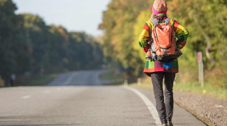 девушка ловит машину автостопом, девушка стоит на дороге с рюкзаком