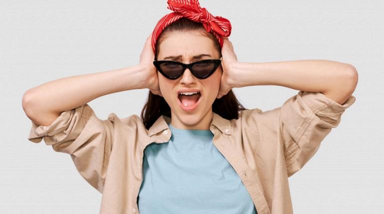девушка закрыла уши руками и кричит, девушка в темных очках и красной косынке