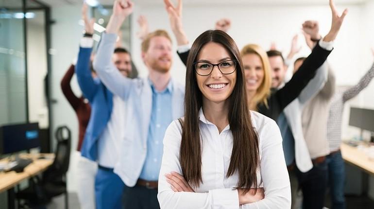 девушка улыбается и счастлива, команда радуется, успех