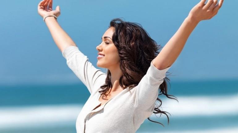 девушка на фоне моря радуется жизни