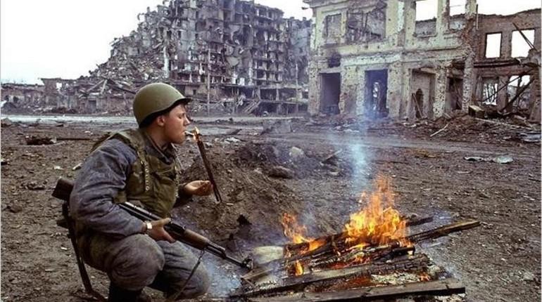 солдат прикуривает от костра, солдат на пожарище в разрушенном городе