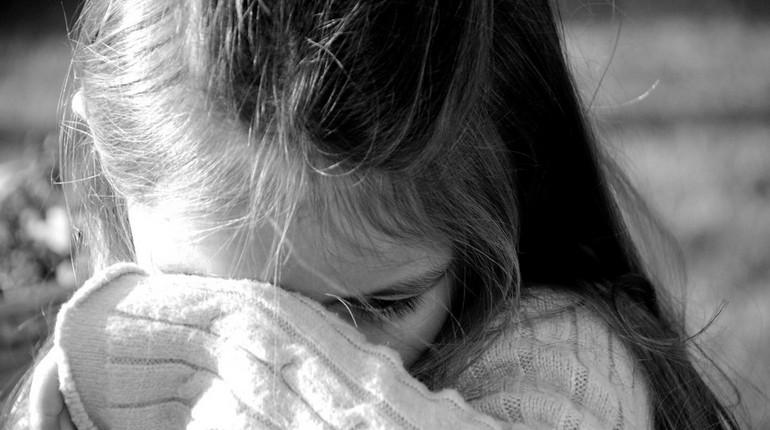 девочка закрыла лицо рукой