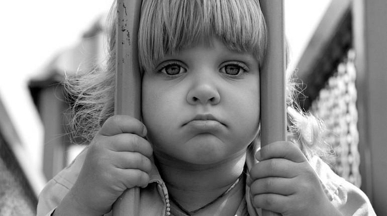 девочка держится за прутья решетки
