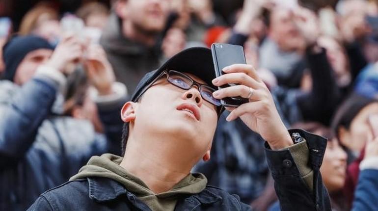 люди смотрят на небо через камеру смартфона, зависимость от телефона