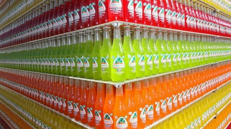 бутылки рассортированные на полках магазина, три полки с напитками разных цветов