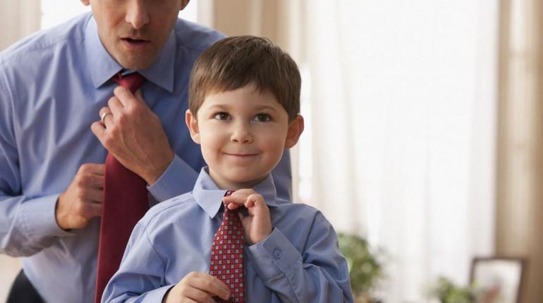 мальчик учится у папы завязывать галстук, маленький и большой в одинаковой одежде