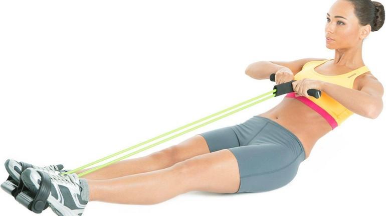 девушка делает упражнения с эспандером