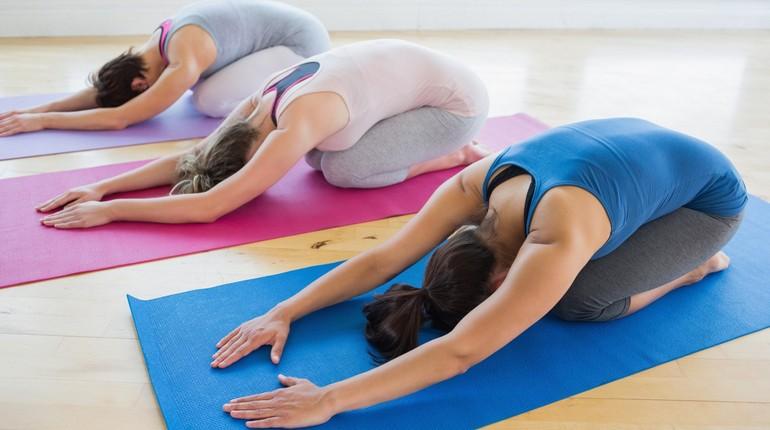 девушки занимаются на ковриках в спортзале