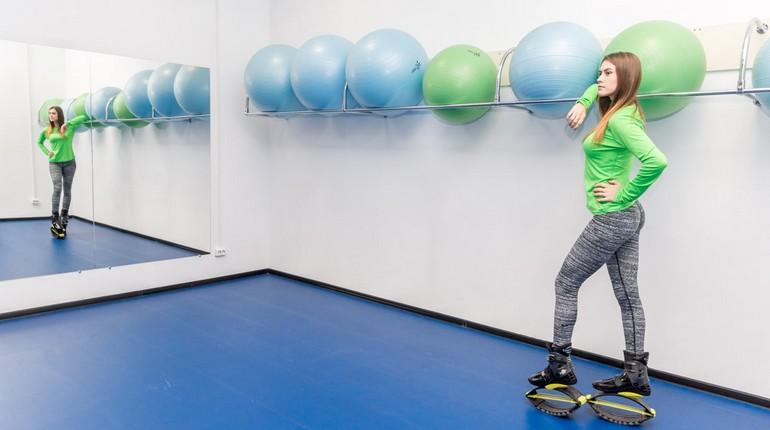 девушка стоит в спорт зале в ботинках джамперах, девушка на тренировке по джампингу