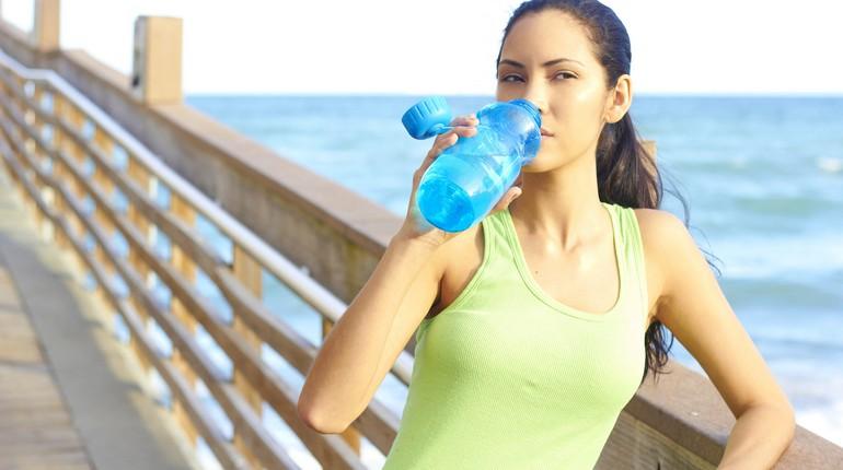 девушка пьет из фитнес-бутылки