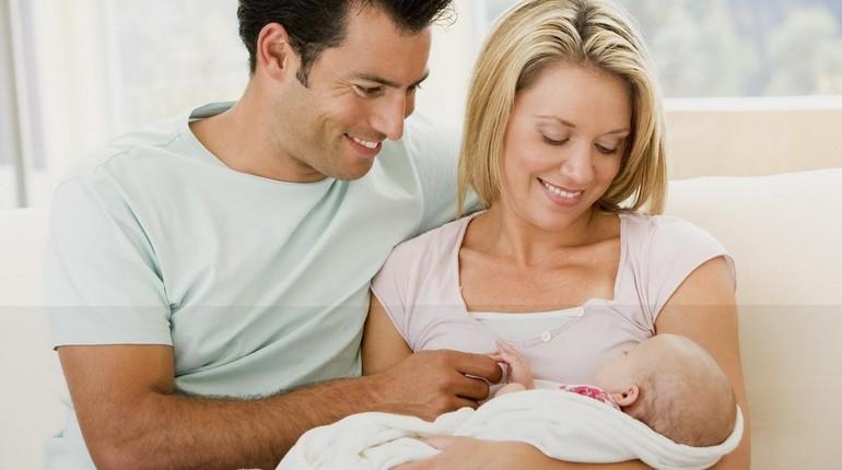 папа и мама с новорожденным ребенком, женщина держит на руках ребенка а мужчина сидит рядом