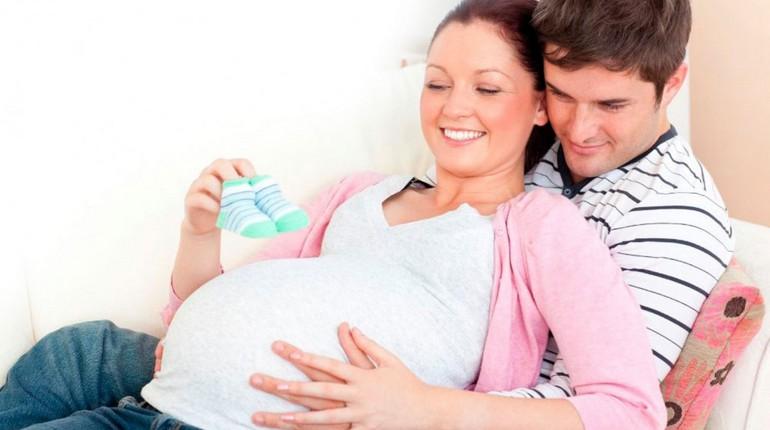 парочка ждет ребенка, мужчина обнимает беременную жену