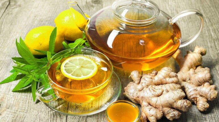 имбирный чай в чайнике и стакане с лимоном