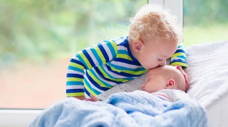 маленький ребенок целует новорожденного младенца
