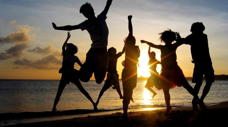 молодежь танцует на берегу моря, компания друзей на берегу