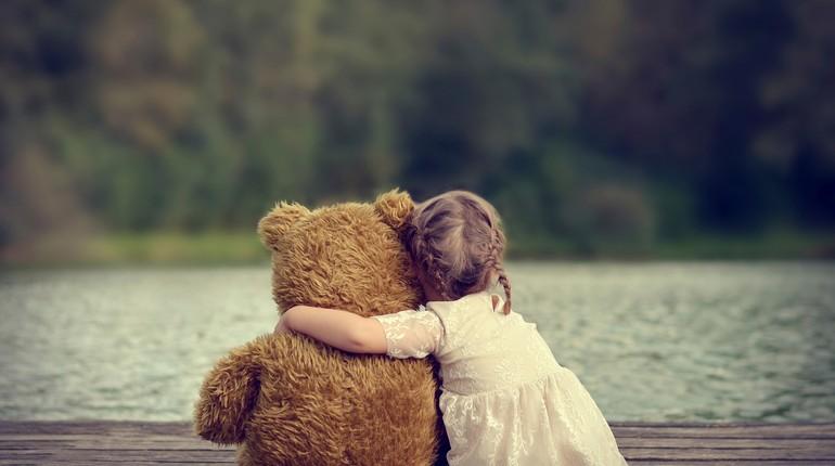 девочка обнимает плюшевого мишку