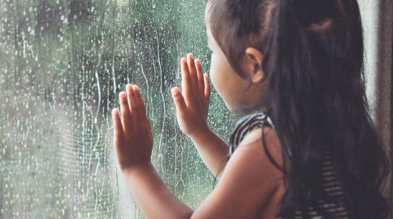 девочка смотрит на дождь сквозь стекло, девочка держит руки на стекле, за окном идет дождь