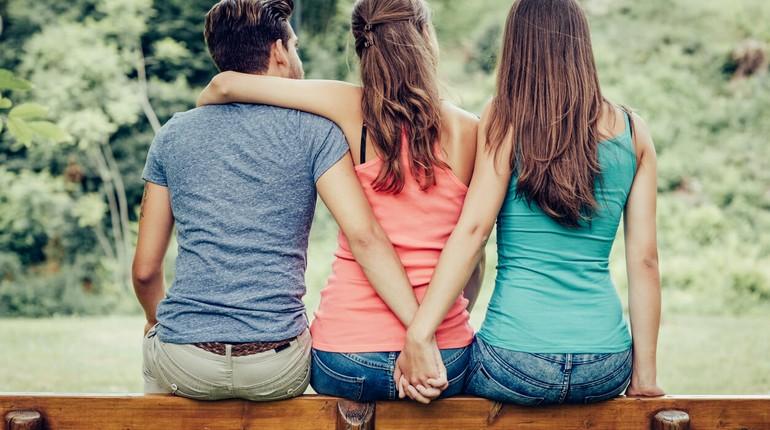 парень держит за руку подругу своей девушки у нее за спиной