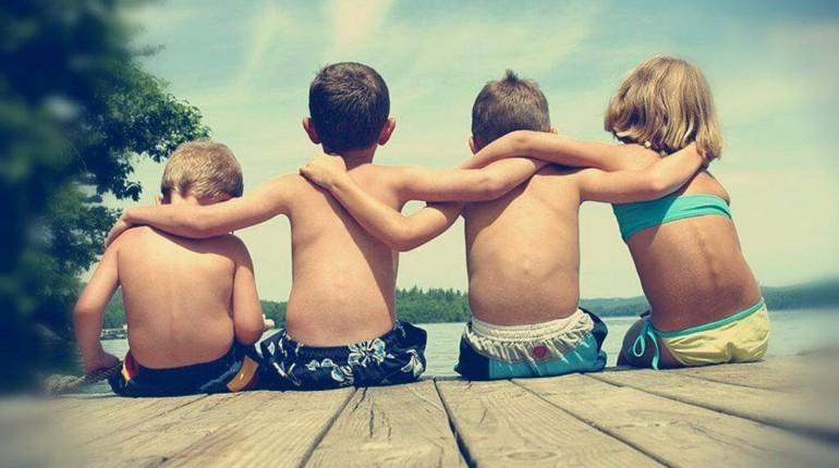 дети обнимаются на деревянном помосте на берегу