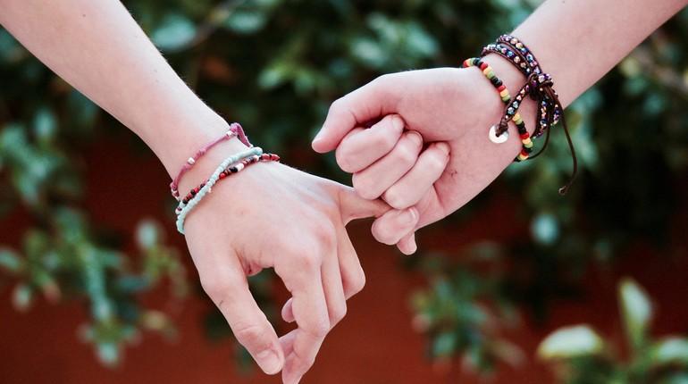 две руки держат друг друга за мизинчик