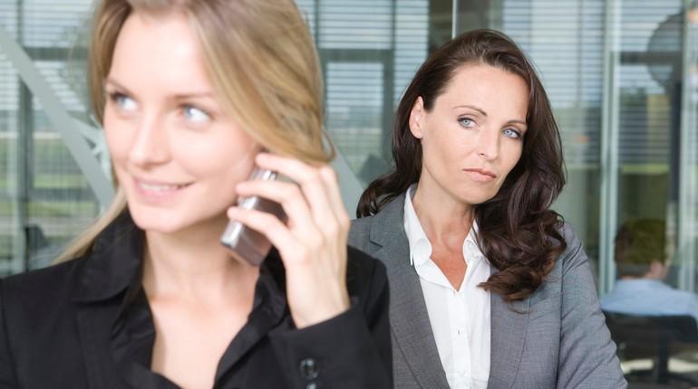две девушки, одна говорит по телефону другая смотрит