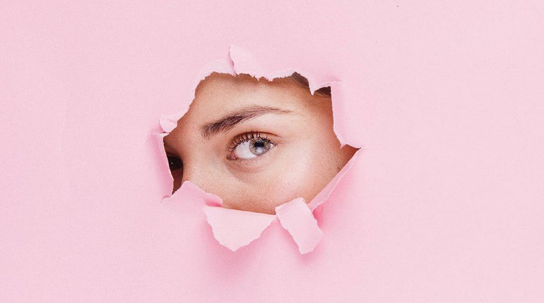 девушка смотрит сквозь дыру в бумаге, глаз девушки через отверстие в бумаге