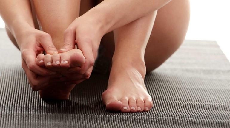ноги косточки на ногах, девушка держится за свои ступни