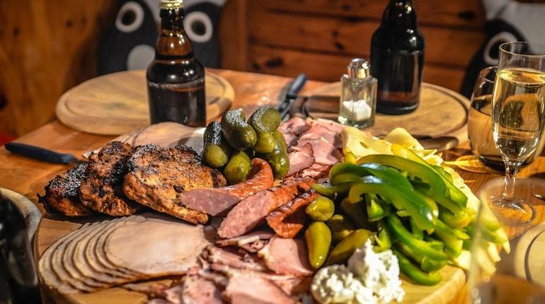 вредная еда, мясо и соленья на столе