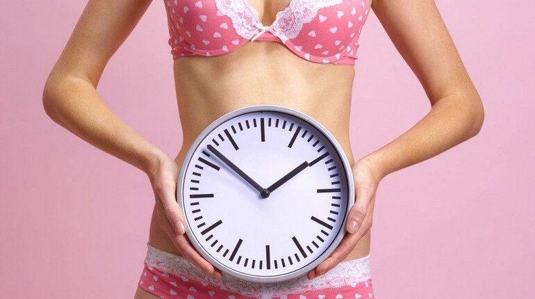 девушка держит в руках часы, девушка в розовом нижнем белье с часами
