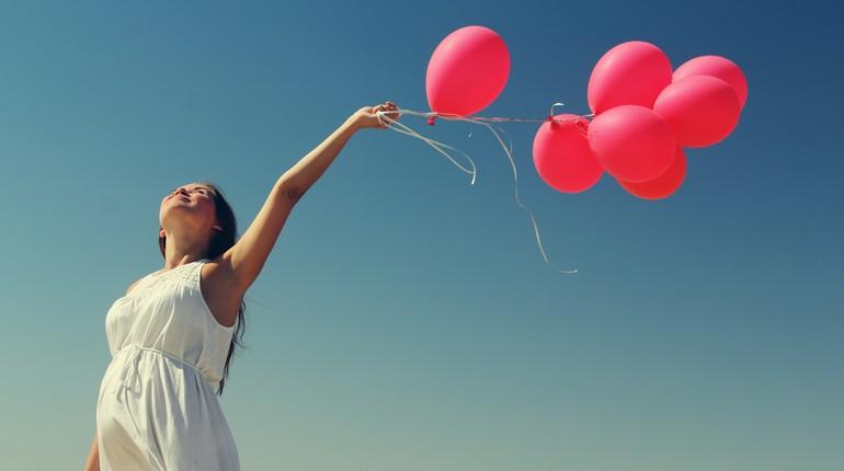 девушка держит в руках шарики
