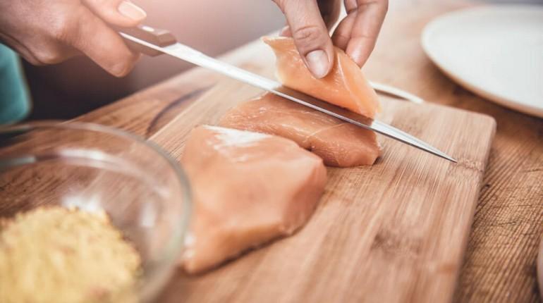 человек режет мясо на досточке, нарезка куриной грудки