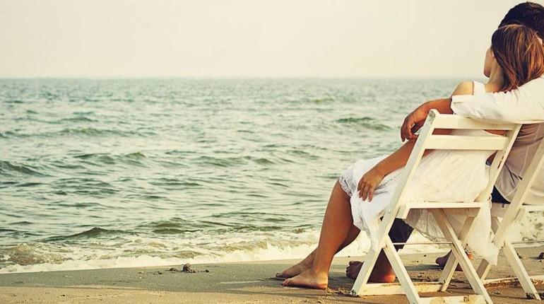 парочка сидит на берегу моря, свидание на пляже